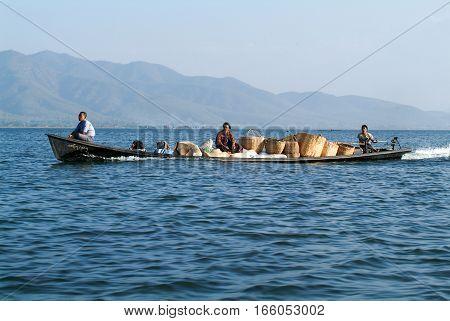 Maing Thauk (lake Inle) Myanmar - 15 January 2010: People transporting goods on a canoe at lake Inle Myanmar
