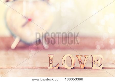 Word Love on wood table with white bokeh and heart alarm clock Valentine's Day background