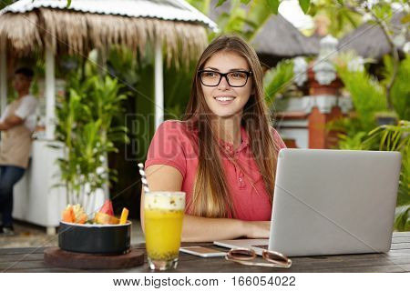 Outdoor Shot Of Young Woman Blogger Wearing Polo Shirt And Rectangular Glasses Sitting In Front Of O