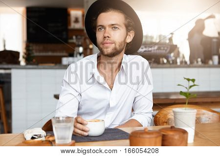 People, Leisure And Lifestyle Concept. Indoor Shot Of Handsome Young Bearded Male Wearing Trendy Hat