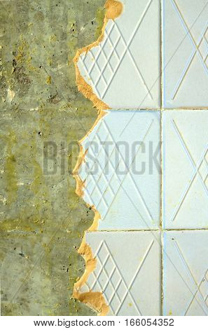 Concrete wall in house with broken ceramic tiles in the process of repair close up
