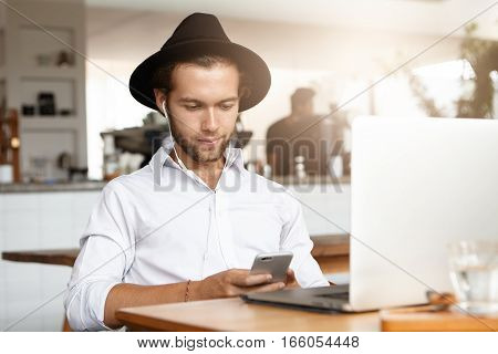Staying Connected. Handsome Young Businessman Watching Video Or Viewing Pcitures Online Via Social M