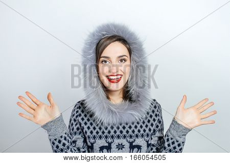 Winter beauty fashion. Beautiful face girl with trendy fur hat gesturing. Emotions. Professional makeup and manicure. Portrait on grey background. Celebrating
