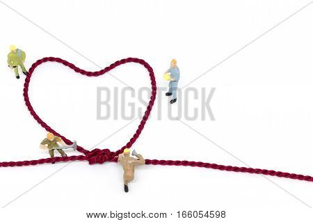 Miniature worker team building Heart Shaped with rope on white background