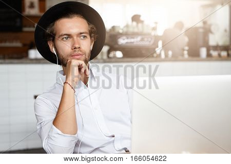 Attractive Young Entrepreneur Holding Hand On His Chin, Having Thoughtful Look, Siting In Front Of O