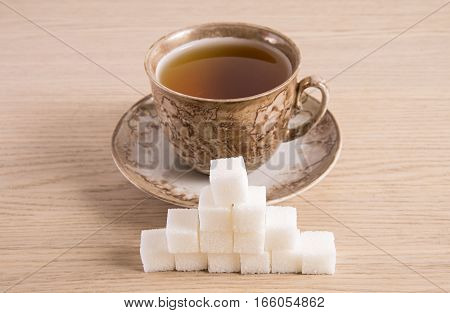 Brown cup hour with cubes of sugar on a light background wood