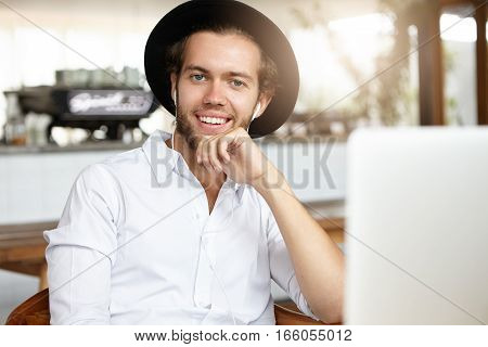 Attractive Young Businessman Relaxing During Lunch At Modern Cafe, Sitting In Front Of Open Laptop A