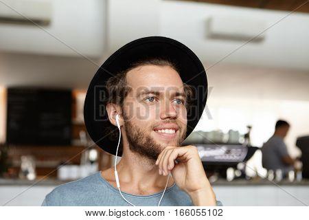 Headshot Of Handsome Young Bearded Student In Black Hat Smiling Joyfully, Enjoying Free Wifi, Making