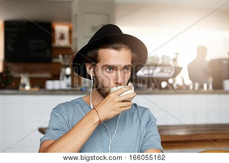 Indoor Shot Of Attractive Young Man In Stylish Hat Drinking Coffee Or Tea, Relaxing At Cafe Alone, L