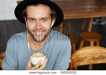 Cheerful Young Student In Casual T-shirt And Trendy Hat Listening To New Album Of His Favourite Arti