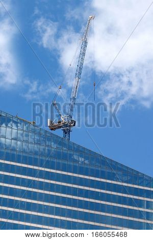 Hoisting tower crane in construction process on top of modern office building over sky with clouds