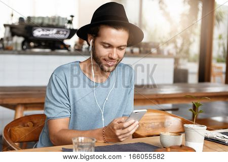 Handsome Bearded Student In Black Hat Texting His Girlfriend Online Via Social Networks, Enjoying Hi