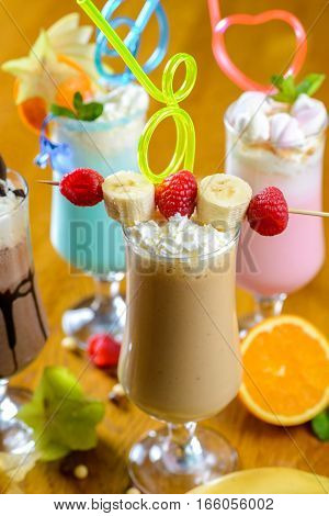 Sweet coctails in high glasses decorated with fruits on table