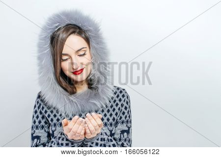 Young and beautiful woman holding a nice Christmas present. Woman hand and emotion.