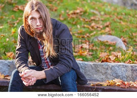 Man Long Hair Sitting On Bench In Autumn Park