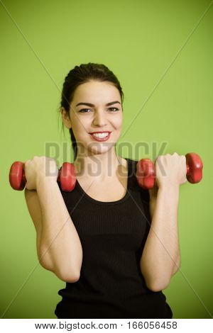 woman doing exercises with dumbbells in the hall