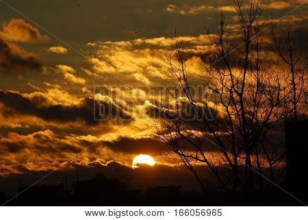 Dark clouds and yellow orange setting sun