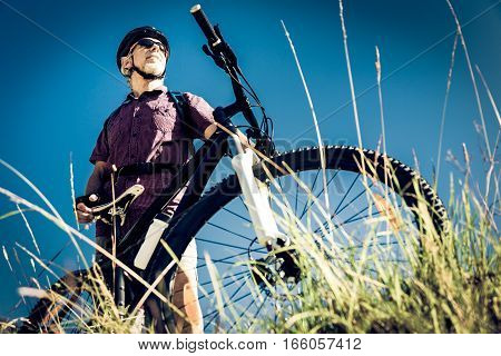 senior with mountain bike standing at top of a hill
