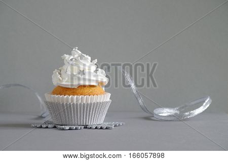 homemade birthday cake with whipping cream and stars in front of a grey background
