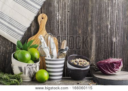 Kitchen tools, olive cutting board on a kitchen against the dark wooden walls with lime in marble bowls, beans in ceramic bowls and salad Radicchio. The horizontal design