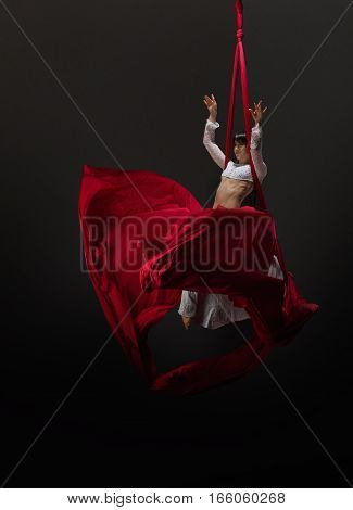 Pretty brunette gymnast in nice white top and leggings exercising on bright red aerial silks and cloth studio shot
