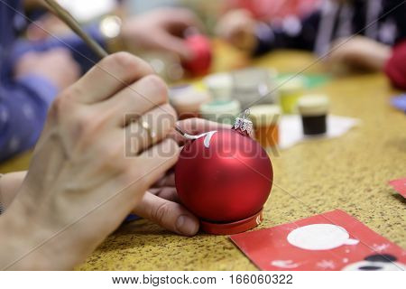 Person painting Christmas toy at table in class