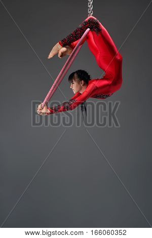 Young brunette gymnast in artistic embroidered sportsuit exercising with a hoop studio shot