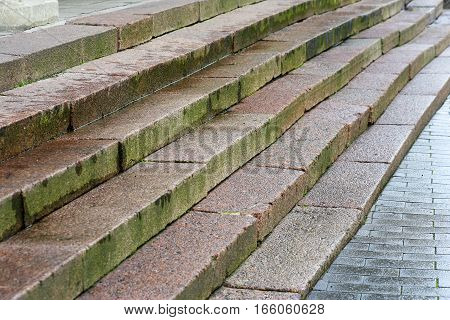 old uneven stair of red granite stone