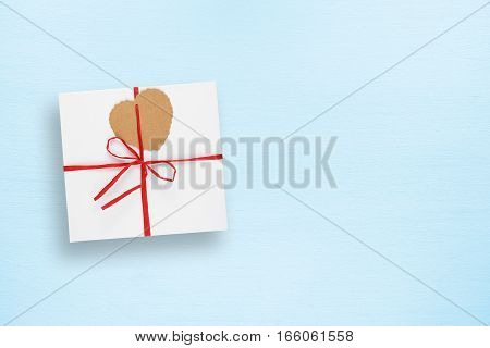 Gift box with tag in form of heart on blue table