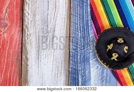 Cinco de Mayo holiday concept in USA with Mexican hat and place mat serapes on rustic wood painted traditional colors of United States.