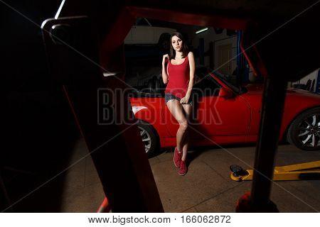 Beautiful girl posing near red car. Brunette in the garage