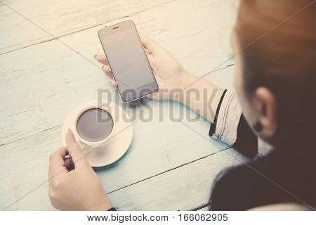 woman hand phone and cup of coffee on wooden table