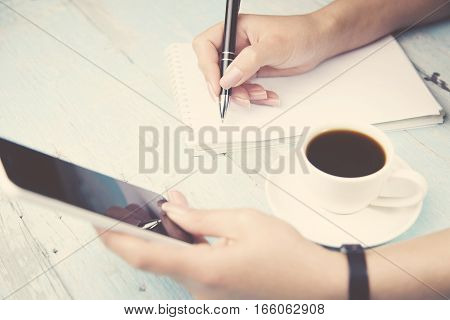 woman hand pen and phone writing on notebook