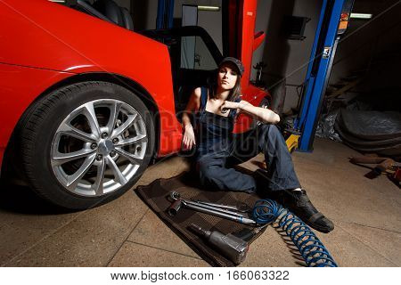 Girl mechanic with a set of tools. Beautiful girl holds the wrench. Brunette repairing the car in the garage