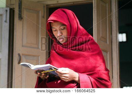 Mandalay Myanmar 17 January 2010: Young monk reading a book at Mahagandayon Monastery on Mandalay Myanmar