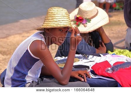 RODRIGUES ISLAND, MAURITIUS - NOVEMBER 10, 2012: A young local boy with a straw hat at the market in Port Mathurin