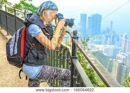 Traveler asian concept. Young travel photographer with professional camera photographing the Victoria Harbour from Victoria Peak, the highest mountain in Hong Kong. Travel and tourism concept.