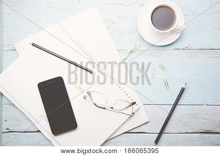 Coffee cup smartphoneglasses and blank notebook on wooden table