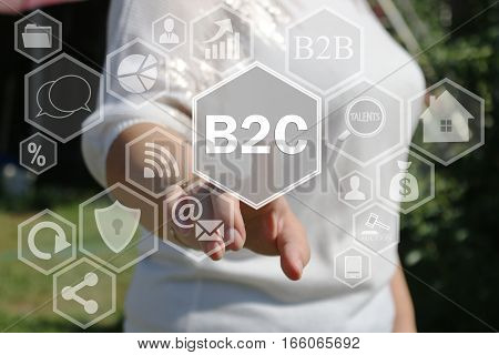 Businesswoman pressing button B2C  on virtual screens in the web network.The concept of The business consultant .