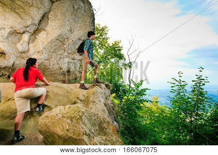 young couple standing at the top of a mountain, enjoying the view