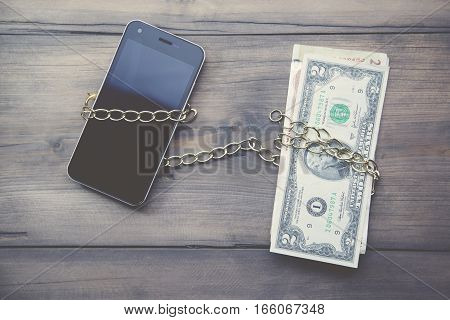 Money chained to the phone on wooden table