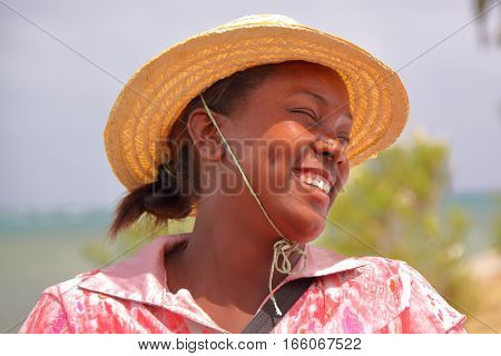 RODRIGUES ISLAND, MAURITIUS - NOVEMBER 10, 2012: Portrait of a  local woman with a straw hat smiling at the market in Port Mathurin
