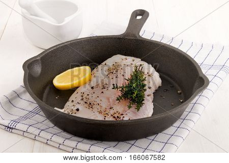 hake fillet with crushed back peppercorn lemon and thyme in a cast iron pan