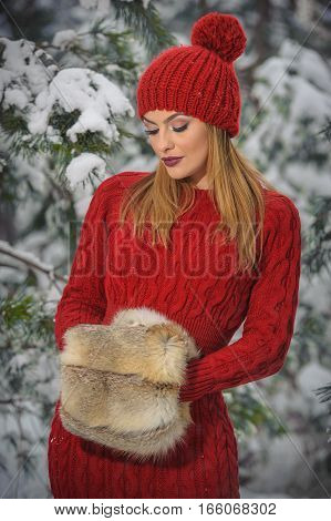 Beautiful woman in red with brown fur cape enjoying the winter scenery in forest. Blonde girl posing under snow-covered trees branches. Young female with snowflakes around in bright cold day, makeup