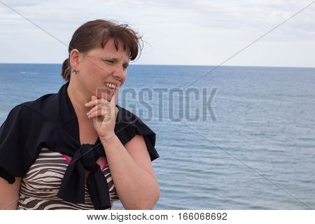 intelligent woman thinks on the mountain in the sea