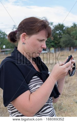 portrait of a woman reading a SMS on mobile summer