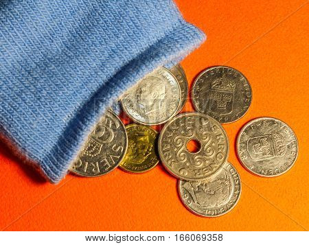 Coins Spilling Out From A Blue Sock
