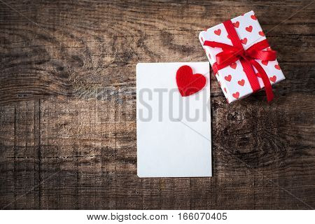 Valentine's Day card  with invitation Card with red heart and copy space for text on wooden Background.