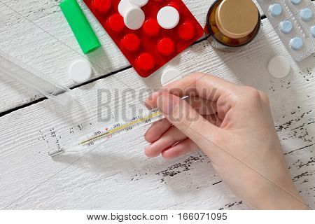 Thermometer In A Female Hand And Various Medications On A White Wooden Table. Temperature Measuremen