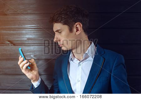 man businessman in suit holding a phone to send SMS or e-mail at work.